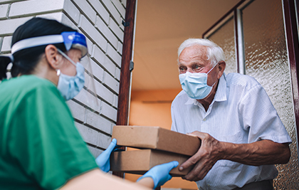 A person delivering food to an elderly person